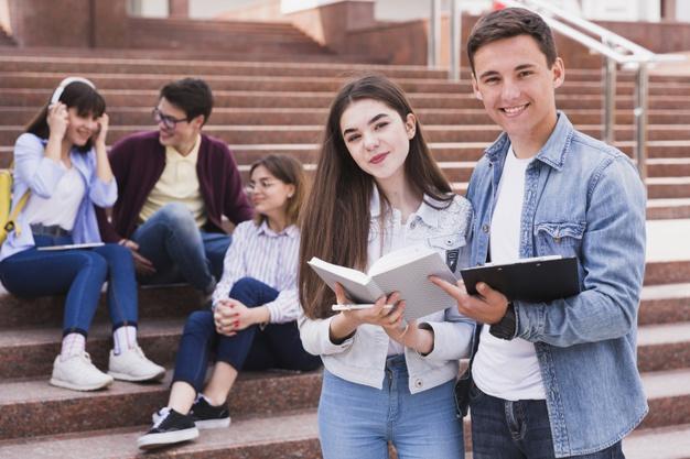 estudiantes-pie-libros-abiertos-mirando-camara_23-2148166405