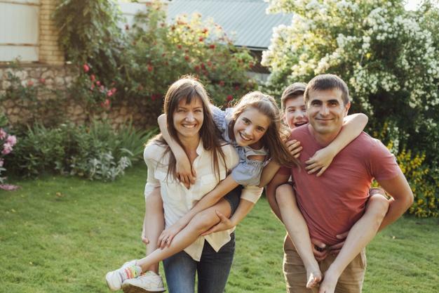 padres-sonrientes-dando-caballito-sus-hijos-parque_23-2148207972